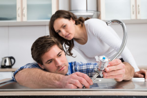 Woman Looking At Plumber Fixing Steel Tap